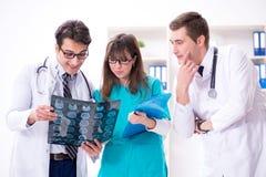3 доктора обсуждая результаты развертки изображения рентгеновского снимка Стоковые Изображения RF