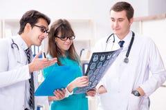3 доктора обсуждая результаты развертки изображения рентгеновского снимка Стоковое Изображение RF
