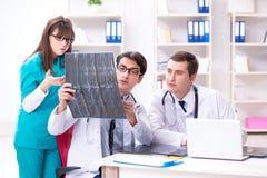 3 доктора обсуждая результаты развертки изображения рентгеновского снимка Стоковое Фото