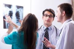 3 доктора обсуждая результаты развертки изображения рентгеновского снимка Стоковая Фотография RF
