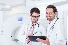 Доктора обсуждая изображения развертки рентгеновского снимка в CT Стоковое фото RF
