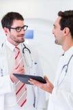 Доктора обсуждая изображения развертки рентгеновского снимка в CT Стоковая Фотография