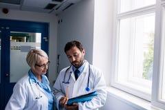 Доктора обсуждая над доской сзажимом для бумаги Стоковые Фотографии RF