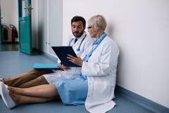 Доктора обсуждая над доской сзажимом для бумаги Стоковое Изображение
