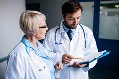 Доктора обсуждая над доской сзажимом для бумаги Стоковые Фото
