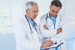 Доктора обсуждая над доской сзажимом для бумаги Стоковое Фото