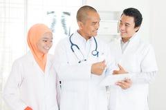 Доктора обсуждая на ПК и больших пальцах руки таблетки вверх Стоковое Изображение RF