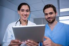 Доктора обсуждая над цифровой таблеткой в больнице Стоковые Изображения RF