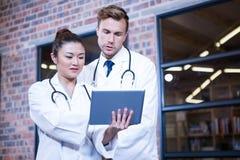 Доктора обсуждая над цифровой таблеткой около библиотеки Стоковое Фото