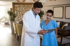 Доктора обсуждая над цифровой таблеткой Стоковое Изображение