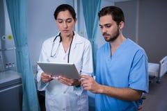 Доктора обсуждая над цифровой таблеткой Стоковые Изображения RF