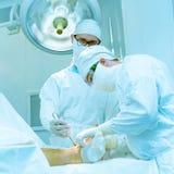 Доктора приводятся в действие дальше пациента Стоковое Изображение