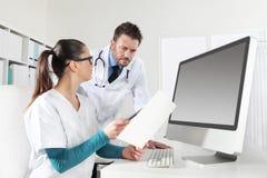 Доктора при медсестра смотря медицинские истории, концепцию советуют с Стоковые Фото