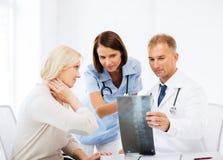 Доктора при пациент смотря рентгеновский снимок Стоковые Фотографии RF