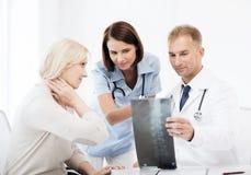 Доктора при пациент смотря рентгеновский снимок Стоковые Изображения