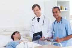 Доктора при рентгенографирование стоя рядом с пациентом Стоковые Изображения