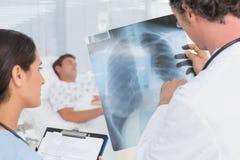 Доктора проверяя рентгеновский снимок пациентов стоковое изображение