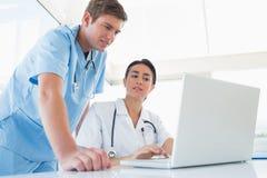 Доктора работая на портативном компьютере Стоковое Изображение