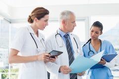 Доктора работая совместно на файле пациентов Стоковые Фотографии RF