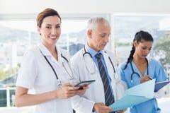 Доктора работая совместно на файле пациентов Стоковая Фотография