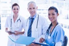 Доктора работая совместно на файле пациентов Стоковые Изображения