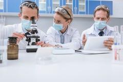 Доктора работая с микроскопом Стоковые Изображения