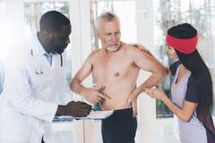 Доктора рассматривают пожилого человека который имеет backache в его назад Стоковое фото RF