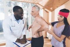 Доктора рассматривают пожилого человека который имеет backache в его назад Стоковая Фотография RF