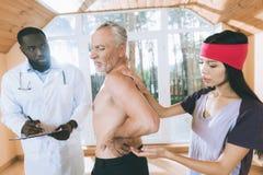 Доктора рассматривают пожилого человека который имеет backache в его назад Стоковое Изображение