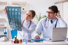 2 доктора рассматривая изображения рентгеновского снимка пациента для диагноза Стоковое Фото