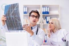 2 доктора рассматривая изображения рентгеновского снимка пациента для диагноза Стоковое фото RF