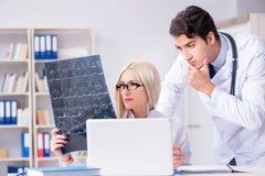 2 доктора рассматривая изображения рентгеновского снимка пациента для диагноза Стоковые Изображения