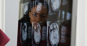 Доктора рассматривая рентгеновские снимки мозга Стоковое Изображение