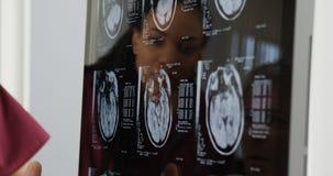 Доктора рассматривая рентгеновские снимки мозга Стоковые Изображения
