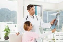 Доктора рассматривая рентгеновский снимок в медицинском офисе Стоковые Изображения