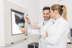 Доктора рассматривая рентгеновский снимок пациента Стоковое Изображение