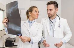 Доктора рассматривая рентгеновский снимок пациента Стоковая Фотография