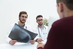 2 доктора рассматривая рентгеновский снимок пациента Стоковое фото RF