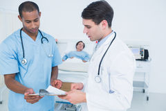 Доктора смотря отчеты с пациентом в больнице Стоковое фото RF