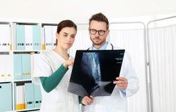 Доктора смотря рентгеновский снимок в медицинском офисе Стоковое Изображение RF