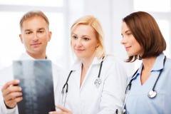Доктора смотря рентгеновский снимок Стоковые Изображения