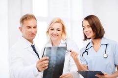 Доктора смотря рентгеновский снимок Стоковое Изображение
