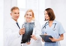 Доктора смотря рентгеновский снимок Стоковая Фотография