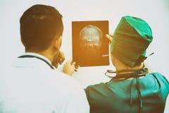 Доктора смотря фильм рентгеновского снимка терпеливого ` s возглавляют Стоковые Изображения RF