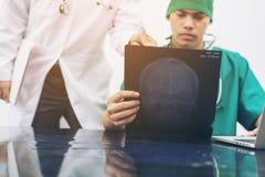 Доктора смотря фильм рентгеновского снимка терпеливого ` s возглавляют Стоковое фото RF