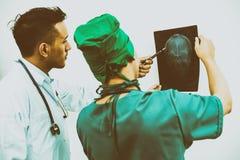 Доктора смотря фильм рентгеновского снимка терпеливого ` s возглавляют Стоковое Изображение