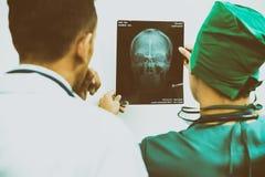 Доктора смотря фильм рентгеновского снимка терпеливого ` s возглавляют Стоковая Фотография