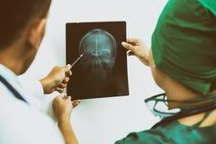 Доктора смотря фильм рентгеновского снимка терпеливого ` s возглавляют Стоковые Фото