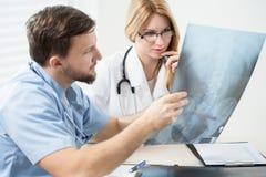 Доктора советуя с рентгеновским снимком Стоковые Изображения