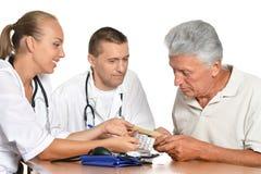 Доктора человека и женщины с пациентом Стоковая Фотография